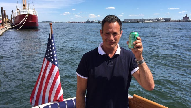 Sam Calagione, co-founder of Dogfish Head Craft Brewery, sailing in Boston Harbor, with a can of SeaQuench Ale.