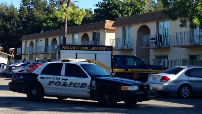 Two police cars and a crime scene unit sit at an apartment colplex off Central Avenue during a homicide investigation.