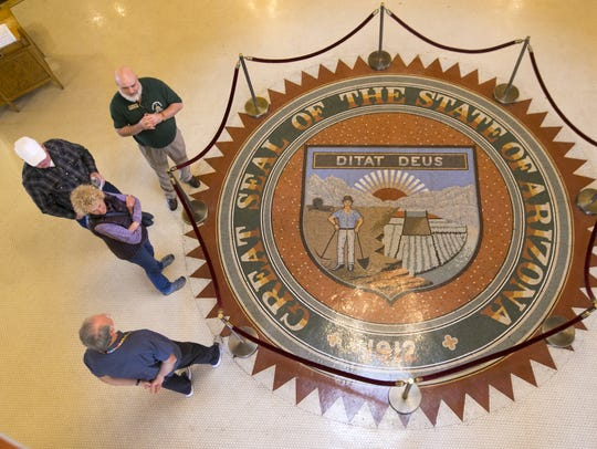 People are seen around the Arizona State Seal in the