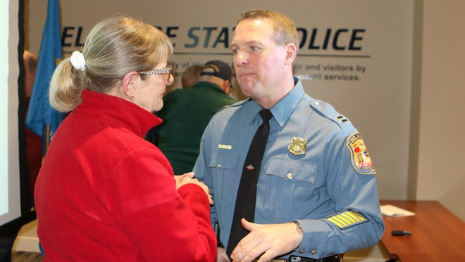 Delaware State Police Troop 3 commander Capt. Joshua Bushweller answers a question about crime in Camden from resident Nancy Ward during a 2017 year in review Thursday evening at Troop 3.