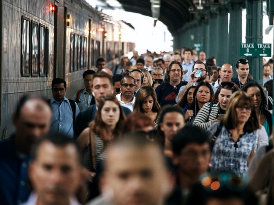 People walk along the railway platform as they arrive at Hoboken Terminal, Monday, July 10, 2017, in Hoboken.