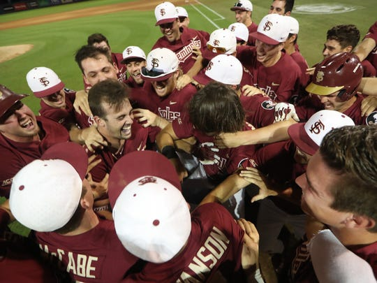 FSU players surround Reese Albert, left center, in