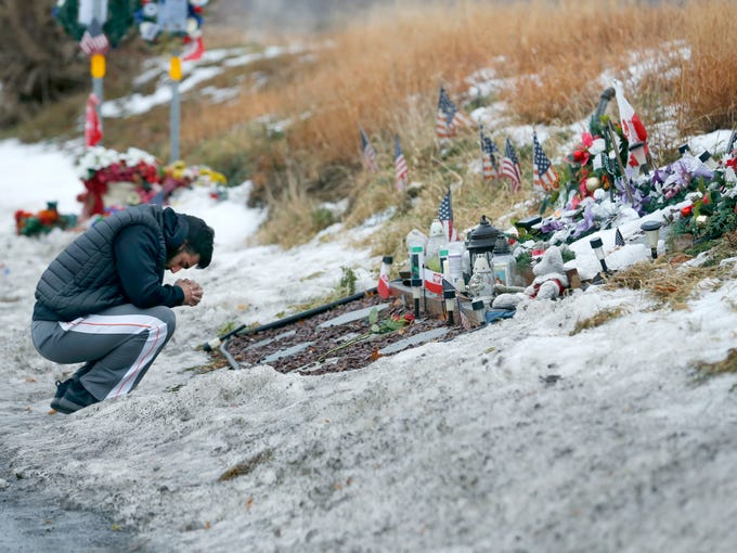 Ryan Damore of Webster prays at the memorial on Lake
