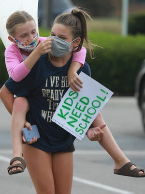 Nola Holderman adjusts the mask of her friend Madden Weldy as they walk to the demonstration for re-opening schools outside the Dublin School Board meeting Tuesday. Holderman hopes to be attending Abraham Depp Elementary School this fall; Weldy hopes to attend Grizzell Middle School.
