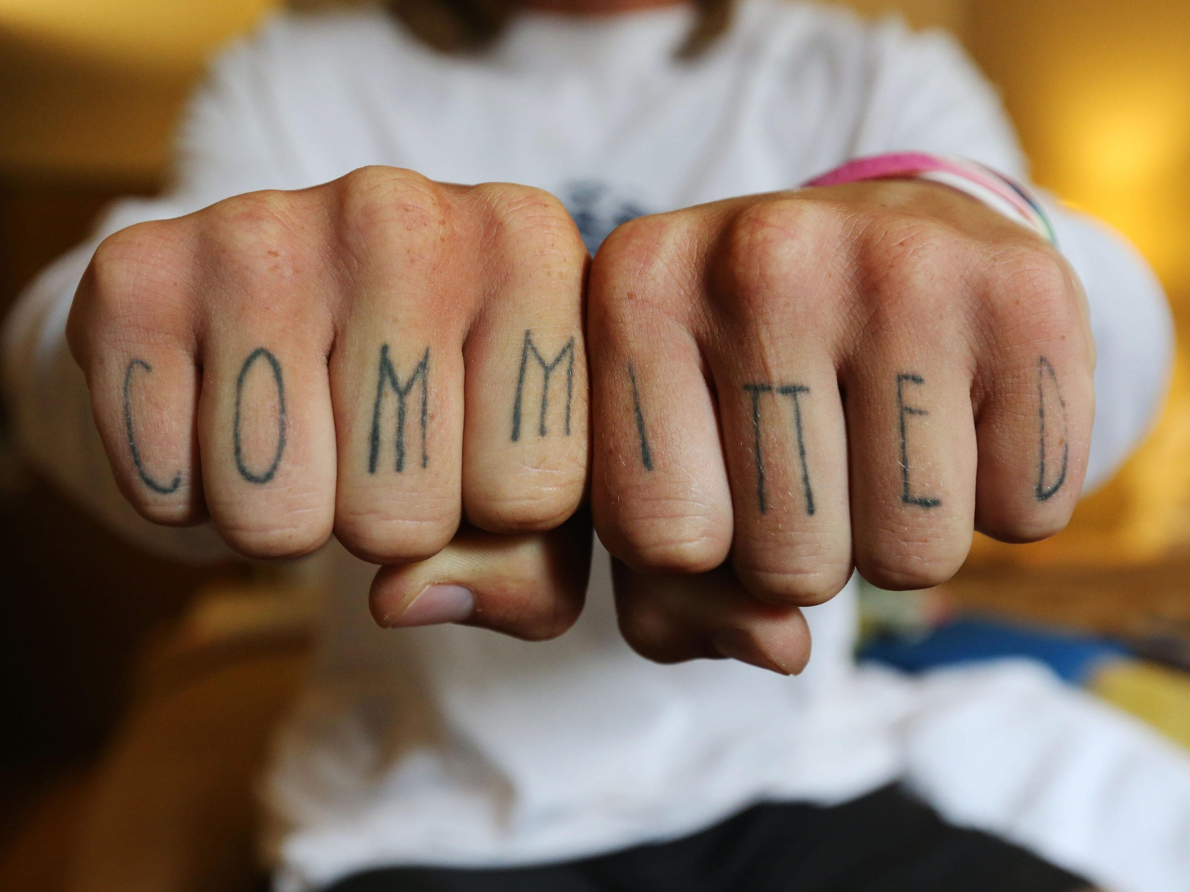 Barefoot runner Jake Brown has the word committed tattooed