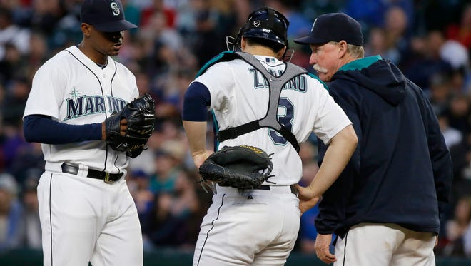 Seattle Mariners pitching coach Rick Waits, right, talks with starting pitcher Roenis Elias, left, as catcher Mike Zunino listens during the sixth inning of the team's baseball game against the Boston Red Sox, Thursday, May 14, 2015, in Seattle.