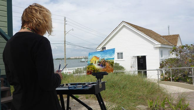 Susan Darienzo paints the boathouse at the House of Refuge Museum.