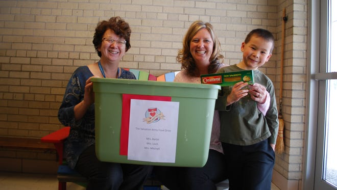 Roberts Elementary School Principal Michelle Hagan, Roberts Elementary School Teacher Sara Morgan, and Caleb Vang hold one of Caleb's collection bins, along with the first donation.