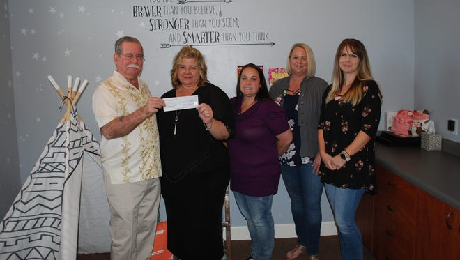 Dixie Elks Charitable Foundation member Garry Gauthier hands a $500 donation to Stacey Garcia, office coordinator with the Washington County Children's Justice Center. With them are Solinda Larsen, victim services coordinator; Julie Cole, resident registered nurse; and Brook Triplett, forensic interviewer.