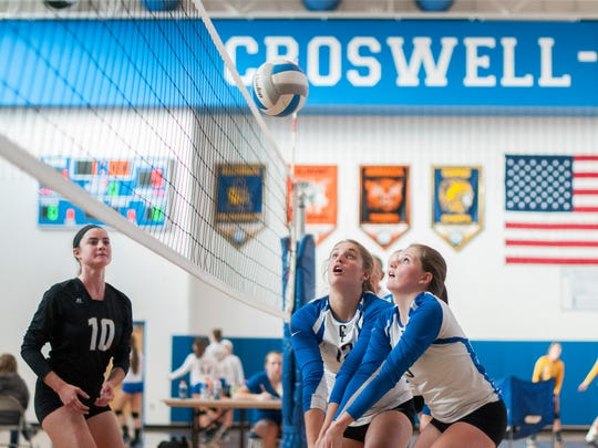 Pioneers' Becca Oden and Brooklynn Paradoski both try and keep the play alive Monday, Oct. 10, during a volleyball match against Almont at CrosLex High School.