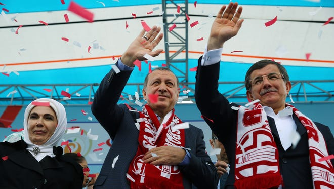 In this April 22, 2016 file photo, Turkey's President Recep Tayyip Erdogan, center, and Prime Minister Ahmet Davutoglu, right, salute together during a ceremony in Antalya, Turkey.