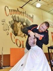 Gene Thomas carefully shaves the head of James Ackroyd