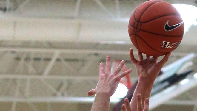 A basketball player takes a shot.