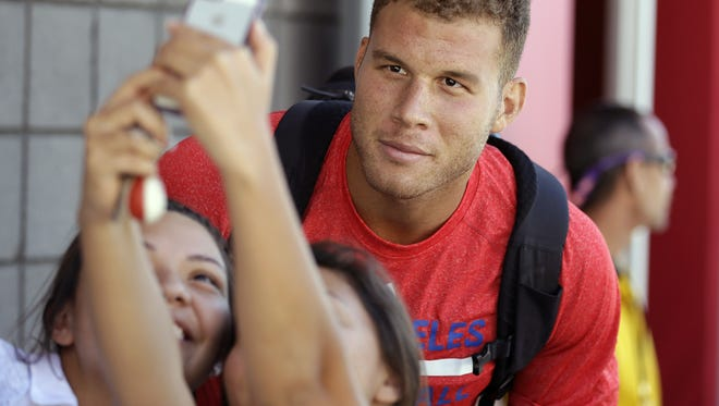 In this file photo, Los Angeles Clippers' Blake Griffin poses for pictures with fans after basketball training camp, Thursday, Oct. 2, 2014, in Las Vegas. (AP Photo/John Locher)