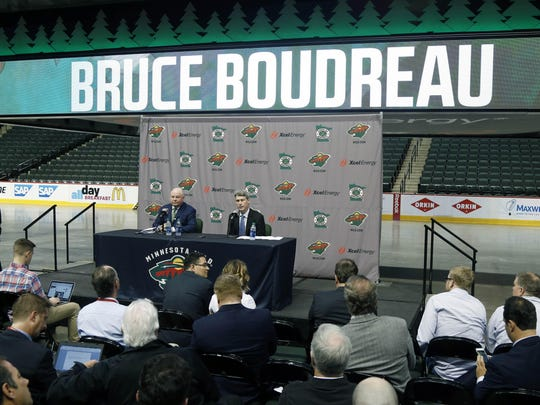 Bruce Boudreau, left, is introduced by Minnesota Wild General Manager Chuck Fletcher, right, as the new Wild head coach during a news conference on Tuesday in St. Paul.