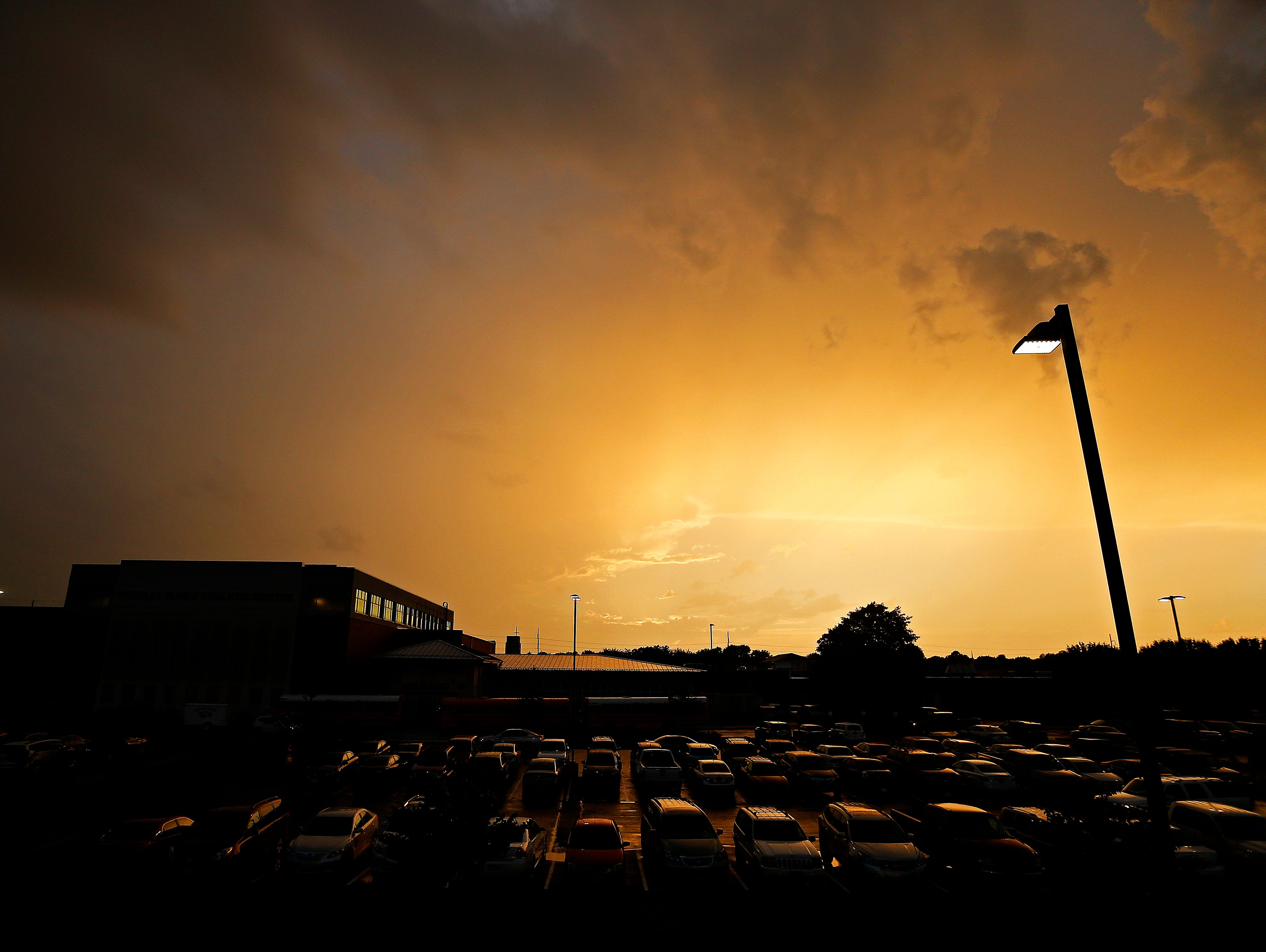 The Sun sets in between storm clouds to the West of a scheduled game between Springfield Catholic High School and Fair Grove High School at Springfield Catholic High School in Springfield, Mo. on Sept. 9, 2016. The game was postponed due to severe weather in the area.