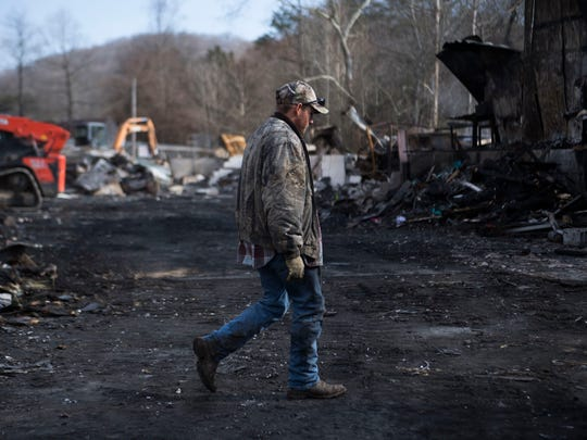 Bradley Swieda walks through debris where a barn once stood at Little Ponderosa Zoo in Clinton, Tenn., Thursday, Dec. 14, 2017. Little Ponderosa Zoo continues to recover after an electrical malfunction caused a fire at the back of their main barn, killing an undetermined number of animals on Dec. 4. Swieda tried to drop off his application to work at the zoo the day of the fire, and has been working there since.