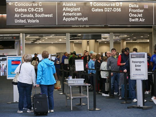 People wait in line to go through security to board