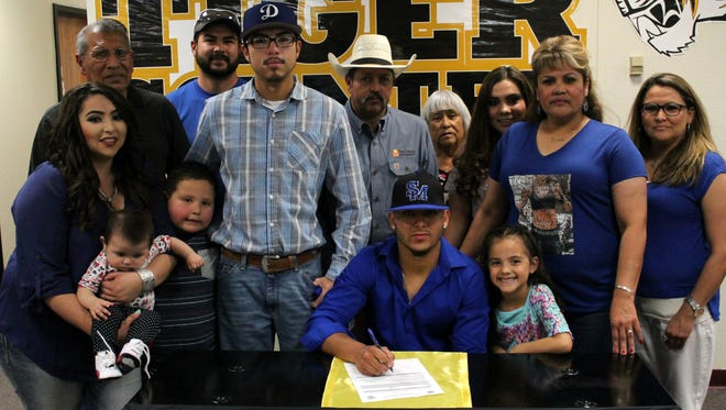 Alamogordo senior Alex Ramirez, front center, poses for a picture alongside his family Wednesday afternoon during his signing ceremony.