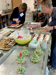 "Workers prep baked goods for the ""Cookie Walk"" at St."