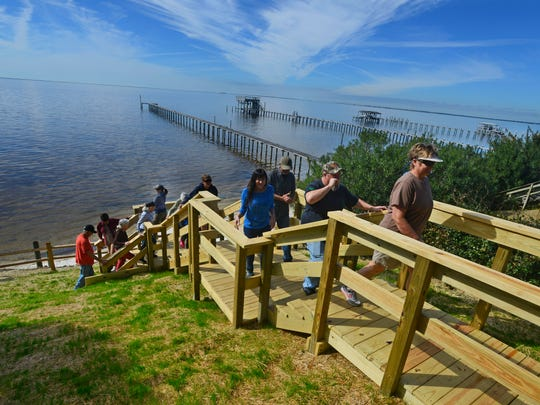 Residents walk up a stairway that leads to the beach at the end of Catawba St. in Gulf Breeze Saturday morning. Some residents believe there should be public access to the beach from the small parcel of land.