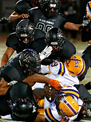 Mesa High running back Kristopher Jackson, at the bottom of the pile, is tackled by Williams Field High players after being stopped during the first quarter in Gilbert on Firday, Oct. 16, 2015.