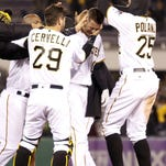 The Pirates mob Jordy Mercer (10) after his RBI single in the 11th inning gave Pittsburgh a 6-5 win against the St. Louis Cardinals at PNC Park on Tuesday.