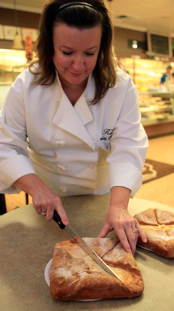 Kim Reschke cuts a  cheese pocket at Wyoming Pastry