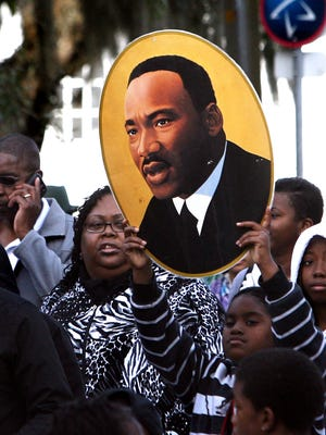 A young girl carries a picture of Dr. Martin Luther King as she marches to the state capitol during the 2013 holiday celebration. A host of local observances of King Day are planned this weekend.