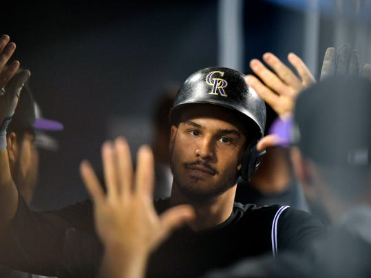 Colorado Rockies' Nolan Arenado is congratulated by teammates after hitting a solo home run during the fifth inning of the teams baseball game against the Los Angeles Dodgers, Tuesday, April 18, 2017, in Los Angeles. (AP Photo/Mark J. Terrill)