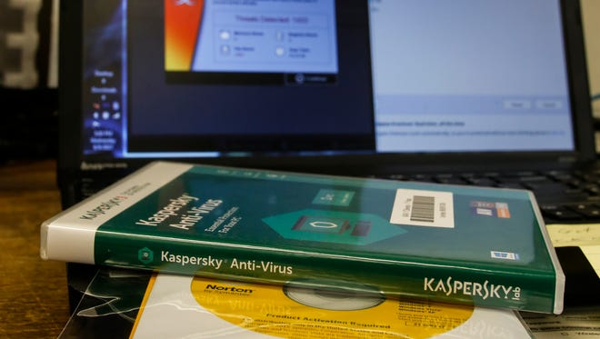 This photo illustration shows a disc containing Kaspersky antivirus software sitting in front of a computer running checks for spyware.