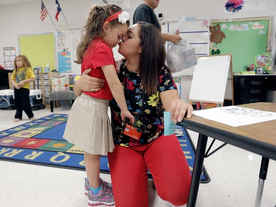 Veronica Acosta kisses her daughter, Mia Acosta, 5, as she drops her off on her first day of kindergarten Monday at John Drugan School in the Socorro ISD.