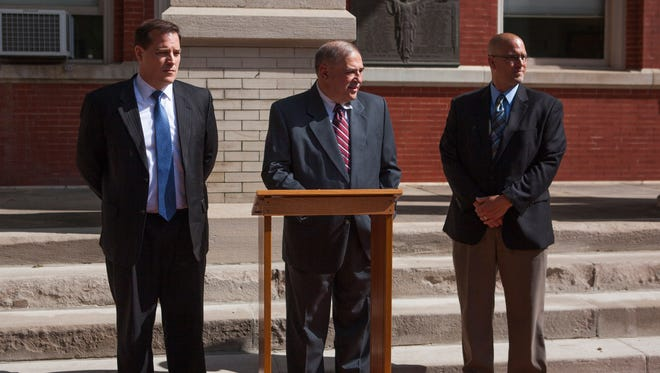 Phil Figura, Chief Prosecutor in the Attorney General's Office, left, A. Lee Ervin, Commonwealth's Attorney for Augusta County, center, and Aaron Leveck, Augusta County Sheriff's office investigator, right, hold a press conference in front of the Augusta County Courthouse to announce the indictment of Charles Almond in the first degree murder of Richard Miller Jr. on Tuesday, May 19, 2015.