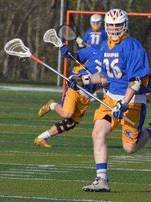 Longsticker Aiden Hynes carries the ball forward in Mahopac's 12-9 win over Brewster.