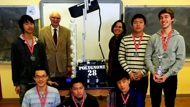 The PolyGnomes pose with their robot, which is extended to display its arm lift and ball tube. Front row, left to right: Bob Yang, Takama Saeki, Danny Chang. Back row, left to right: James Yang, coach James Madsen, assistant coach Lisa Krogh, Chester Lee, Brian Frei. Absent: Tobias Gilbert.
