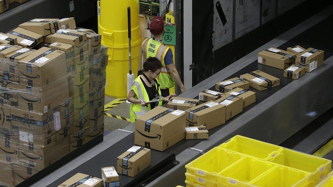 FILE - In this Feb. 9, 2018, file photo packages move down a conveyor system were they are directed to the proper shipping area at the new Amazon Fulfillment Center in Sacramento, Calif. Amazon said Monday, Sept. 14, 2020, that it will be hiring another 2,000 people in Pennsylvania to keep up with a surge of online orders. The company said the new hires will help pack, ship or sort orders, working in part-time and full-time roles. Amazon said the jobs are not related to its typical holiday hiring.