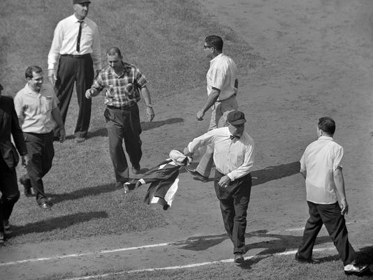 Umpire Jocko Conlan yanks a Cuban flag from marchers at Wrigley Field in Chicago, Aug. 4, 1963. (AP)