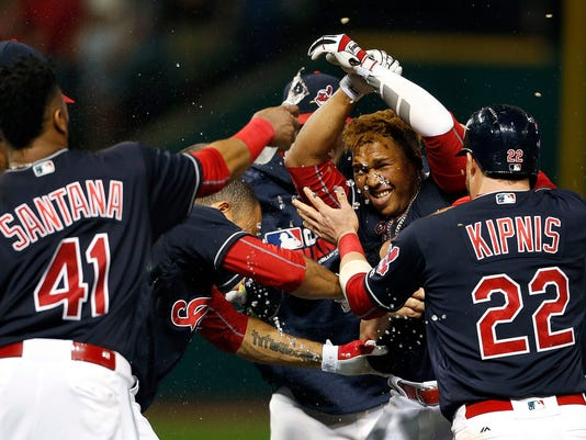 Cleveland Indians' Jose Ramirez, second from right, is mobbed by teammates after hitting a game winning single off Detroit Tigers relief pitcher Justin Wilson during the tenth inning of a baseball game Saturday, Sept. 17, 2016, in Cleveland. The Indians won 1-0. (AP Photo/Ron Schwane)