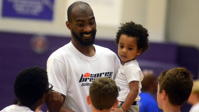 Corey Brewer talks to campers with his son, Sebastian, during Brewer's annual basketball camp at Portland High School last year.