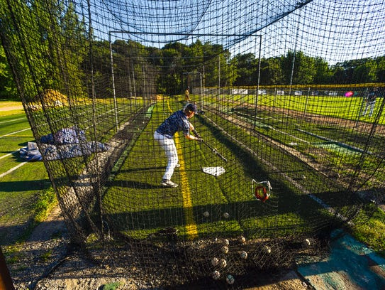 Players warm up in the batting cage before a game between