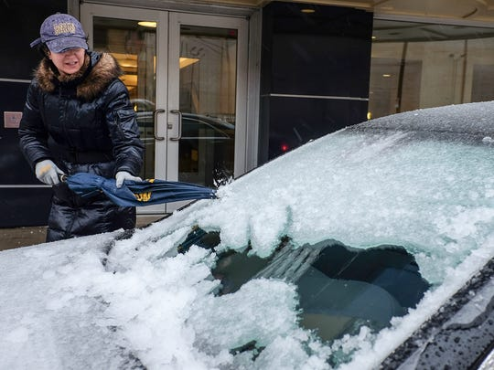 A woman uses an umbrella Sunday to chip away at the ice accumulation on her windshield in downtown Lansing . A storm dumped nearly an inch of ice overnight.