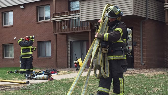 Firefighters clean up at the scene of an apartment fire at 401-14th Ave. SE.