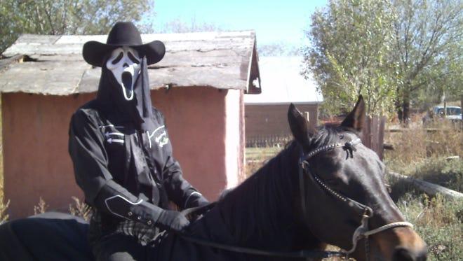 The Ghost of Billy the Kid rides Belle, his black bay mare, during Lincoln's Día de los Muertos.