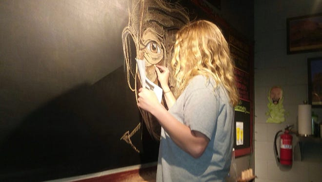 Sarah Buschmann works on an Anthony Bourdain tribute in chalk art at Indianapolis' Bier Brewery.