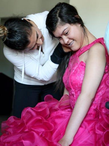 Maribel Vargas holds her daughter Maribel's hair during