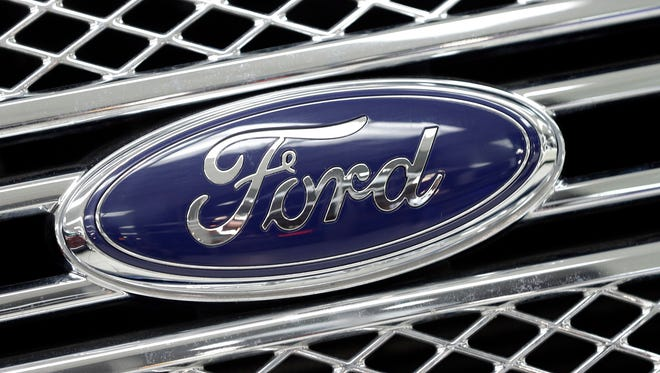In this Jan. 5, 2015, photo, the Ford logo shines on the front grille of a 2014 Ford F-150, on display at a local dealership in Hialeah, Fla. Ford will build a new $1.6 billion factory in Mexico, creating about 2,800 jobs and shifting small-car production from the U.S. The announcement Tuesday, April 5, 2016 comes at a time when moving jobs to the south has become a major issue in the U.S. presidential campaign.