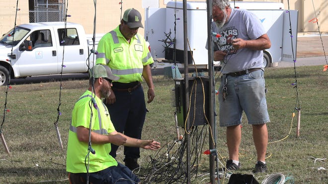Fort Smith Parks Department employees Brian Penix, from left, Fermin Mendoza and Chris Holycross, work on the wireing for the holiday lights display, Monday, Nov. 9, in the White Dairy Park at Grand Ave. and N 10th Street.