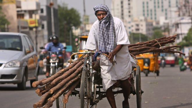 A laborer covers himself with a cloth to protect from the sun as he pulls a rickshaw carrying wooden logs on a hot summer afternoon in Hyderabad, India, Friday, May 20, 2016.