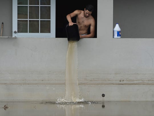 A resident bails water from a flooded home in the aftermath