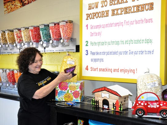 Abilene Specialty Popcorn Store owner Nora Carpenter places bagged gourmet popcorn and other treats into a gift pack on Thursday. The store opened Friday.